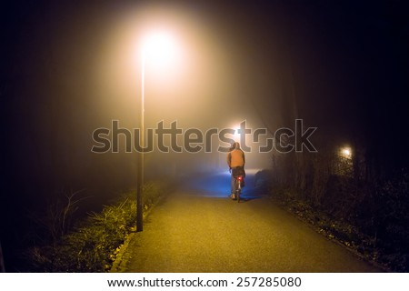 Night foggy ride on bike with street lights (diffused, toned). Sports concept.  - stock photo