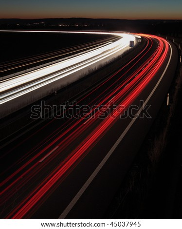 Night highway (Cars in a rush moving fast on a highway  (speedway) in the UK at the nightfall - stock photo