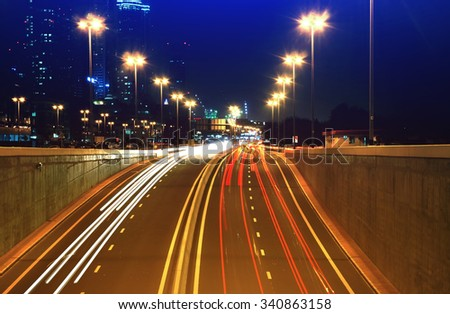 Night highway with moving traffic lights on it. Road with many cars in big night city. - stock photo
