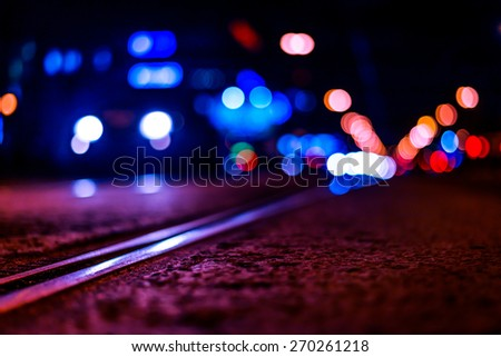 Night highway with rails, car go over it. View from the level of asphalt, image in the purple-blue toning