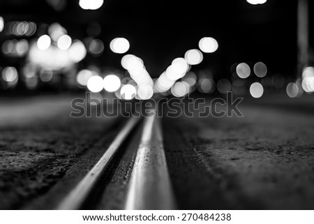 Night highway with rails, cars go over it. View from the level of asphalt, in black and white tones - stock photo