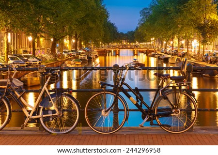 Night  illumination of Amsterdam canal and bridge with typical dutch houses, boats and bicycles, Holland, Netherlands. Focus on the background - stock photo