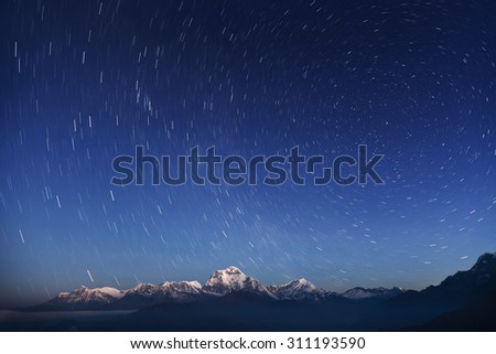 Night laconic landscape. Starry sky over the snowy mountains.  - stock photo