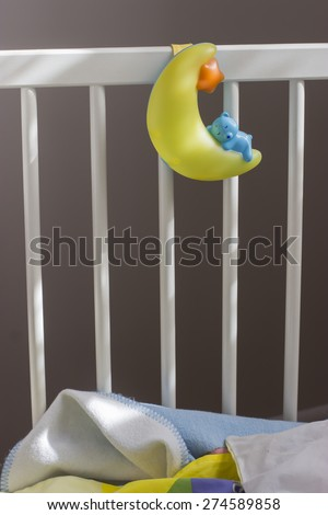 night lamp in the form of a blue bear sleeping on the yellow moon, hanging on a white wooden baby's bed with a blanket - stock photo