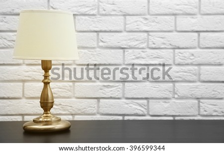 Night lamp on the desk on white brick wall background - stock photo