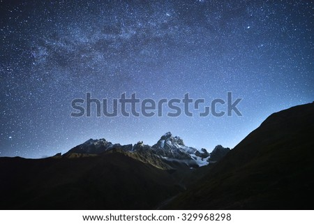 Night landscape. Starry sky with the Milky Way over the mountains. Mount Ushba in the light of the rising moon. Main Caucasian ridge. Zemo Svaneti, Georgia  - stock photo