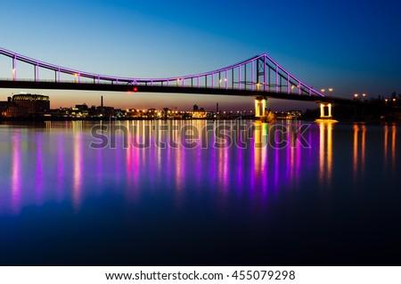 Night landscape. The city of Kiev, Ukraine, Europe. Pedestrian bridge across the Dnieper River. Beautiful lighting and reflection in water - stock photo