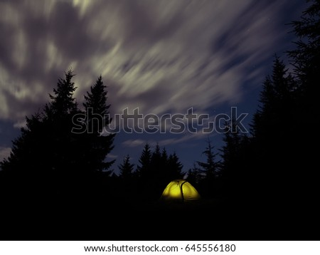 Night landscape with a glowing tourist tent and a night sky surrounded by spruce.