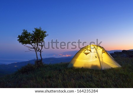 Night landscape with a tent in the mountains. The light from the lantern in a tent. Camping in the countryside. Crimea, Ukraine, Europe - stock photo