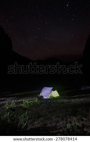 Night landscape with lone, populated and lit easy-to-pitch (pop-up) tent standing on a mountain pasture under the starry sky. Outdoor lifestyle and sleeping under stars concepts and background.  - stock photo