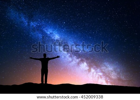 Night landscape with Milky Way. Silhouette of a standing young man with raised up arms on the mountain. Beautiful Universe. Travel background with blue night starry sky - stock photo