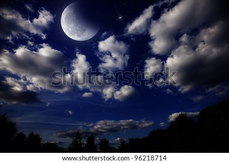 Night landscape with the moon in a cloudy sky above dark forest - stock photo