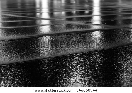 Night light reflection on wet paving slab after rain. Black and white image with selective focus - stock photo