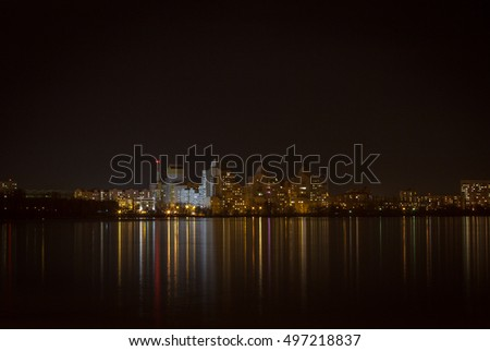 Night lights of city buildings reflected in the water. long exposure