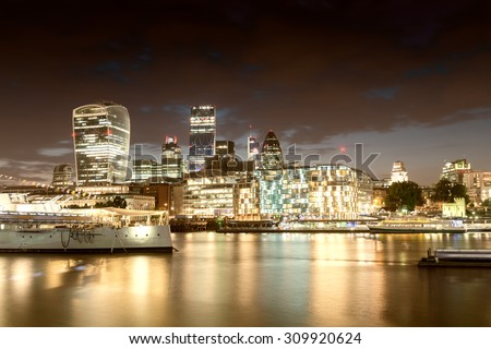 Night lights of London. Buildings reflections near river Thames. - stock photo