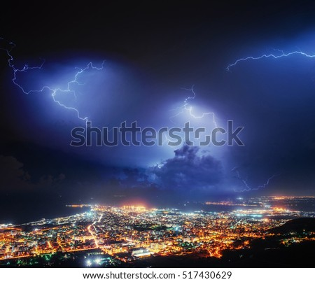 Night Lights Of The Coastal City From The Height. Lightning Strike On The  Cloudy Dark