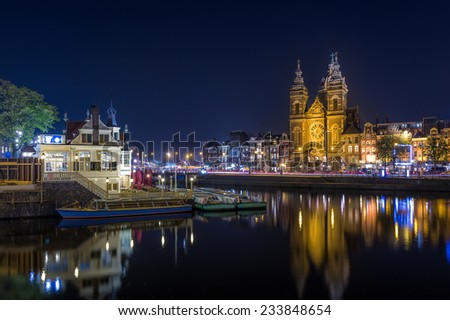 Night long exposure photo of St. Nicholas church and Amsterdam channels.