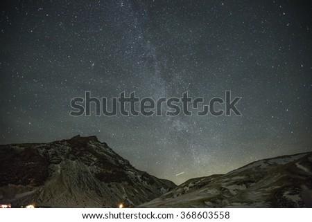 Night mountain landscape and milky way on background illuminated - stock photo