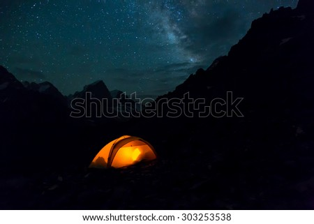 Night mountain landscape with illuminated tent. Silhouettes of mountain peaks and edges night sky with many stars and milky way on background illuminated orange tent on foreground - stock photo
