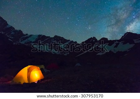 Night mountain landscape with illuminated tent. Silhouettes of snowy mountain peaks and edges night sky with many stars and milky way on background illuminated orange tent on foreground - stock photo