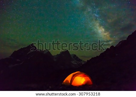 Night mountain landscape with illuminated tent. Silhouettes of snowy mountain peaks and edges night sky : glowing tent - memphite.com