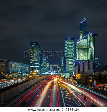 Night multi-lane road with skyscrapers of the La Defense, Paris, France. Long exposure - stock photo