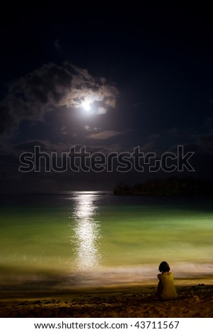 Night ocean with moon and moonlight reflection on water. Solitude.