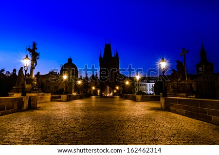 Night over Charles bridge with its statuette and the roofs of the old building, Prague, Bohemia, Czech Republic - stock photo