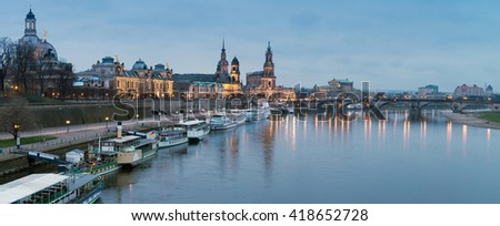 Night panorama of Dresden Old town with reflections in Elbe river and passenger ships - stock photo