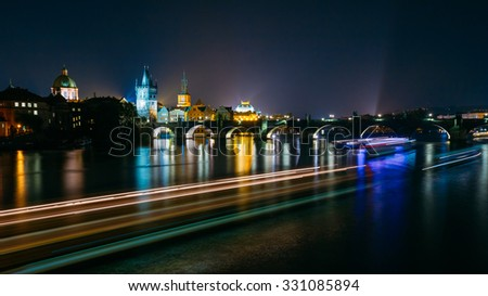Night panorama of illuminated Charles Bridge in Prague, Czech Republic. Reflections of illumination in Vltava river.