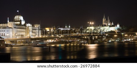 Night panorama of Prague castle and New Town with reflection in Vltava river.