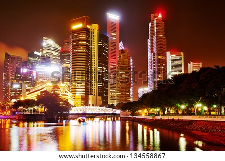 Night panorama of Singapore downtown with reflection in the river