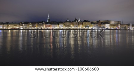 Night panorama over Stockholm Old Town with Skeppsbron, church towers and the Royal Palace - stock photo