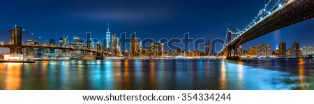 "Night panorama with the downtown New York City skyline and the ""Two Bridges"": Brooklyn Bridge and Manhattan Bridge, viewed from Brooklyn Bridge Park - stock photo"