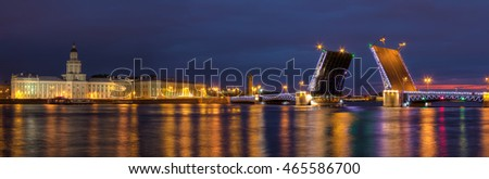 Night panoramic view on illumunated open Palace Bridge, Neva River and buildings on the embankment, St. Petersburg, Russia