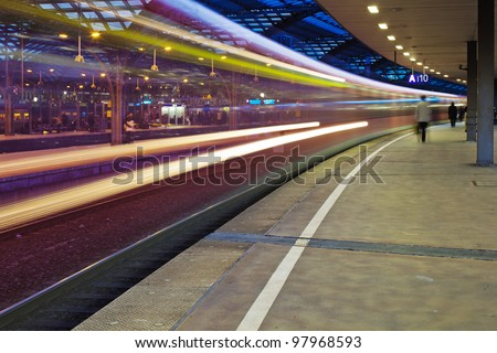 night photo of a departing train at the train station with motion blur