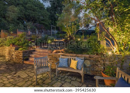 Night photo of a private beautiful hillside Garden with wooden bench, pillows and chair.   - stock photo