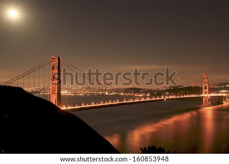 night photo of the Golden gate Bridge with the full moon  - stock photo