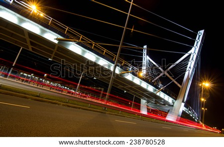 Night photography of a busy road with bridge - stock photo