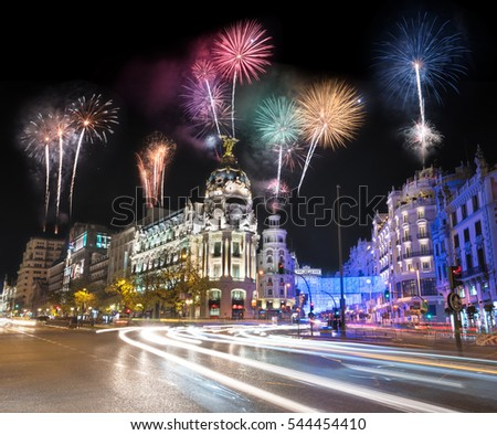 Night photography of Madrid cityscape fireworks display celebration, Gran Via street with rays of traffic light. Madrid, Spain.