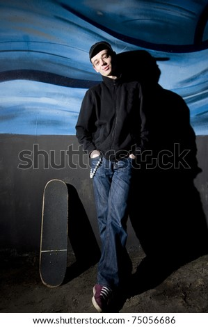 Night portrait of young man with skateboard - stock photo