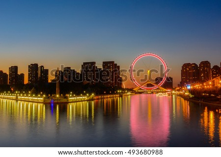 Night scene cityscape of Tianjin ferris wheel,Tianjin eyes with light blue background in twilight time. Most modern  popular landmark in Tianjin city China.