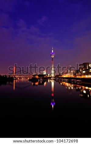 Night scene in Dusseldorf at the Rhine river with the Rheinturm Tower, toned image. - stock photo