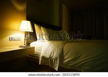 Night scene in hotel room, nightstand with lamp - stock photo