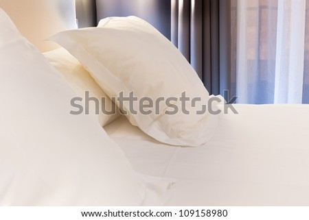 Night scene in hotel room: prepared fresh bed - stock photo