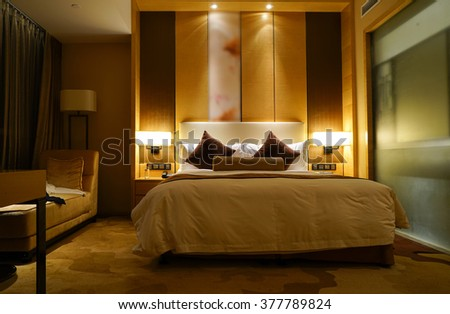 Night scene in luxury hotel room, nightstand with lamp. - stock photo