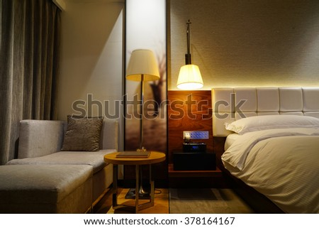 Night scene in luxury hotel room, nightstand with lamp.