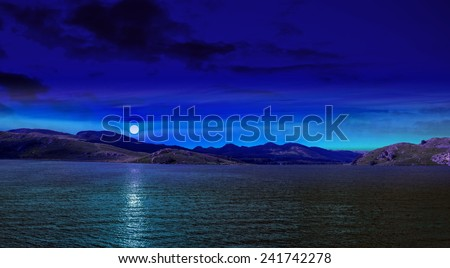 Night scene in mountain with full moon reflected in sea blue water.  - stock photo