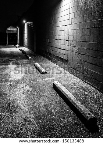 Night scene in the parking lot of an abandoned shopping plaza. - stock photo