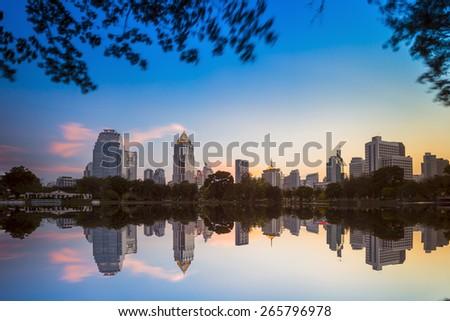 Night scene of Bangkok skyline at dusk from Lumphini Park - stock photo